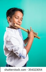 10 year old indian cute boy playing flute /musical instrument, isolated over green background