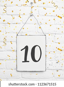 10 years old birthday party card text with golden confetti, number ten, metal plate white brick background