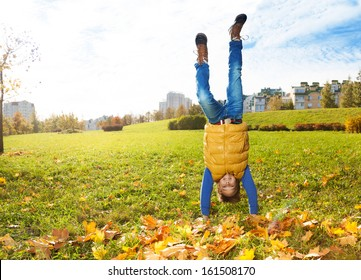 10 years old boy standing on hands outside on sunny autumn day balancing