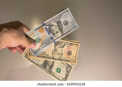 100 10 and 1 American dollar bills being held between fingers on hand made presentation back side white background conceptual American money dollar photo shoot.