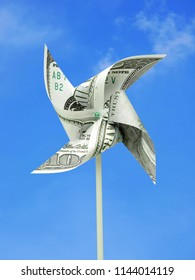 100 American dollar banknote cut into toy windmill shot over blue sky