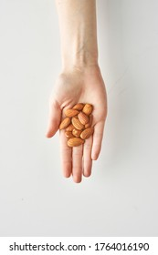 100 calories of healthy snack of almonds in woman's hand isolated on white background, healthy food and lifestyle