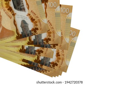 100 Canadian dollars bills lies in small bunch or pack isolated on white. Mockup with copy space. Business and currency exchange concept