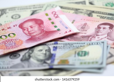 100 China yuan stack over US dollar bill, Thai Baht, banknote, finance trade business, forex, wealth, pile of cash, paper money, financial with selective focus on Thai baht bill.