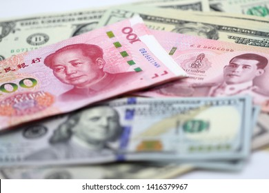 100 China yuan stack over US dollar bill, Thai Baht, banknote, finance trade business, forex, wealth, pile of cash, paper money, financial with selective focus on China yuan bill.