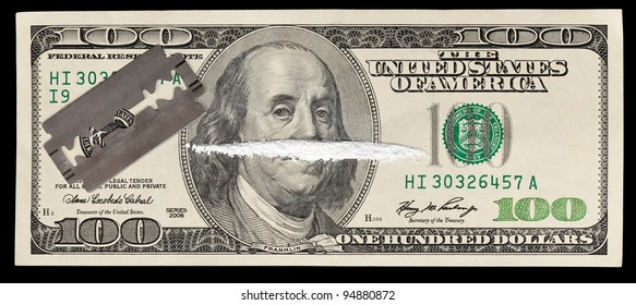 A 100 dollar bill with a line of white powder and razor on it.