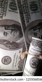 $100 dollar bills on black background