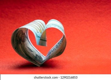 100 dollars. A hundred dollar bill folded in the shape of a heart on a red background. Copy space. Concept of money, love and a gift for Valentine's Day.