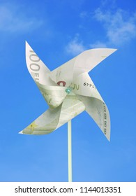 100 Euro banknote cut into toy windmill shot over blue sky