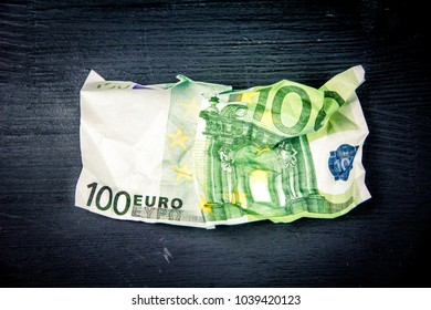 100 euro crushed banknote on a black wooden background