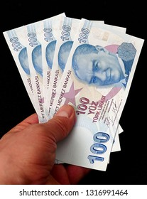 100 Turkish Lira in the hands of a person,