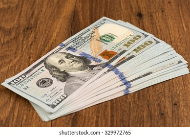 100 US dollars banknotes on wooden background