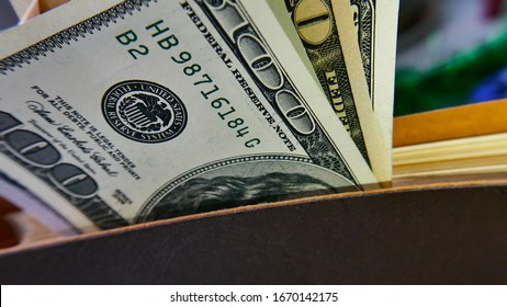 100 US dollars and diary. Closeup.  Closed book (notebook) with gilded (gold) pages. Businessman with money. Concept of business, entrepreneurship and finance.