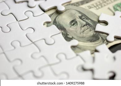 100 USD bill under Blank white puzzle jigsaw : economic crisis management concept
