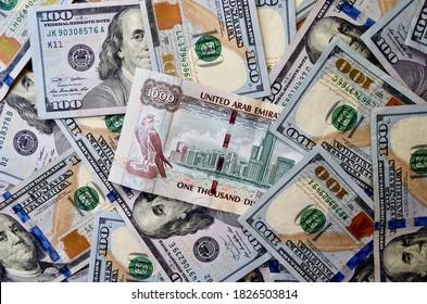 1000 Dirham banknote on top of American dollars currency, top view of mixed USA dollars banknotes. UAE paper money. Dirhams and US dollars exchange rate.