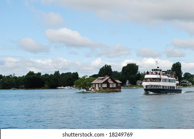 1000 Islands - August 1, 2008: Photo of small house and cruise ship on the St. Lawrence River. USA - Canada border.