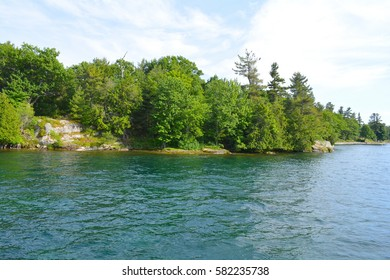 1000 Islands Region. Sunny summer day. Rocky Island on the St. Lawrence River crowned with pine trees. Kingston, Ontario, Canada. Unfiltered, natural lighting. Tourist routs.