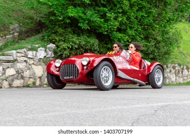 1000 Miles 2019, Brescia - Italy. May 14, 2019:  The historic Mille Miglia car race. Two girls rushing in a beautiful red vintage car on the race Mille Miglia on the road in the castle of Brescia