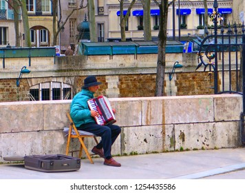 10.01.2016.  the unidentified street musician near Notre Dame cathedral and Seine river, Paris, France