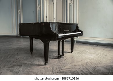 10.01.2021. Saint Petersburg. Russia. An old grand piano stands in an old abandoned manor house. Translation of the inscription - red October.