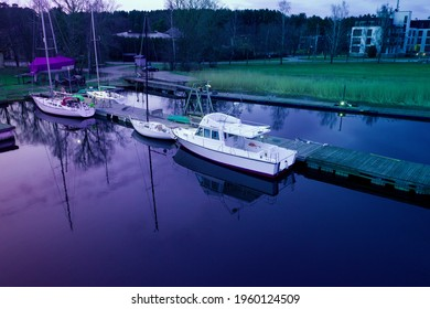 10-04-2021 Jurmala, Latvia. Aerial drone top view photo of small motor boat or yacht standing near the wooden pier in the river or lake.