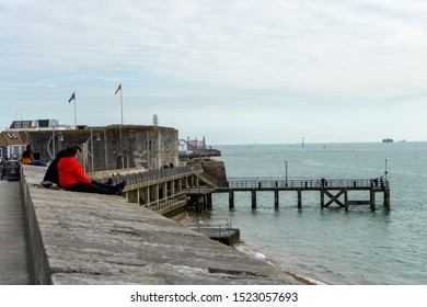 10/05/2019 Portsmouth, Hampshire, UK A couple sat talking sitting on the walls at Old Portsmouth looking out to sea