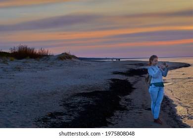 10.05.2021, Riga, Latvia. Beautiful woman on the beach taking photo with camera