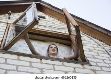 10.07.2017 Russia, Togliatti, Cottage PTO The girl opens the windows at the cottage