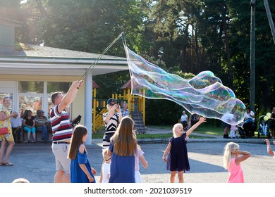 10.07.2021, Tuja, Latvia, A group of young adults making giant soap bubbles on an early summer afternoon. . High quality photo