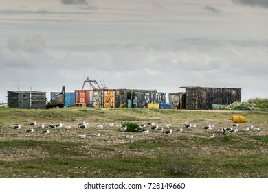 10/09/2017 Dungeness, UK, dystopian scene of rusty sea containers on wasteland beach