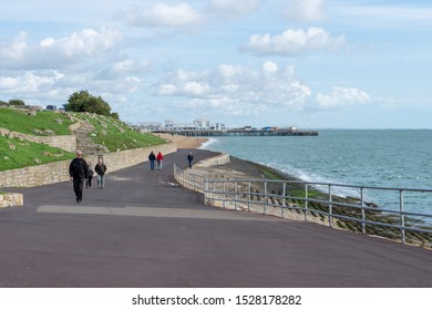 10/09/2019 Portsmouth, Hampshire, UK people walking along the beach at southsea portsmouth with south parade pier in the background
