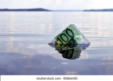100-euro note sinking into the water, shot on a lake