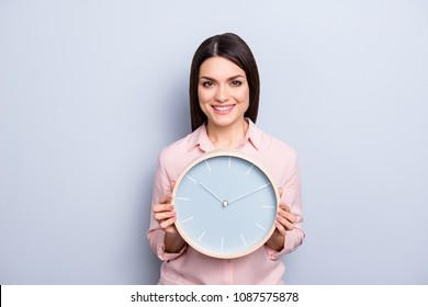 It's 10:10 o'clock. Portrait of charming pretty positive cheerful woman having round clock in hands looking at camera isolated on grey background
