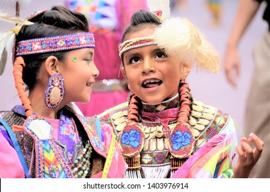 10-10-2014 Rapid City, South Dakota - Two young Native American junior Fancy Shawl  dancers chat while coming off of the arena floor during the Black Hills Powwow.