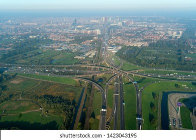 10-10-2018, Den Haag, Holland. Aerial view of a multilevel cloverleaf with underpass, overpass and railway. It is the intersection were highway A4 and motorway A12 connect with skyline The Hague.