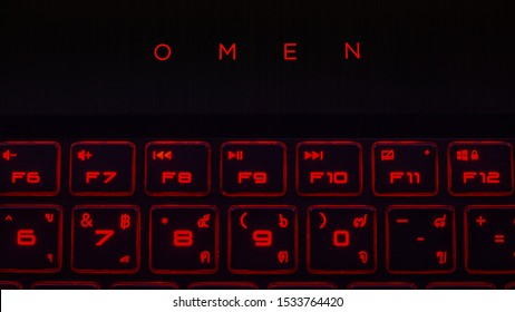 10/17/2019: Bangkok, Obvious and saturated red color Hp Omen logo with two rows of red light function and character keyboard button shot in dark room circa place