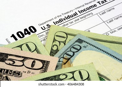A 1040 income tax form with United States currency. The corner of the Twenty Dollar bill obscures the year to add to the image usefulness.