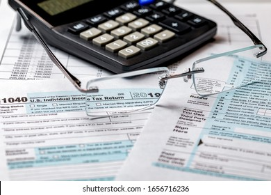 1040 income tax return form 2019 with calculator and focus through glasses. Concept of filing taxes, payment, refund, and April 15, 2020 tax deadline