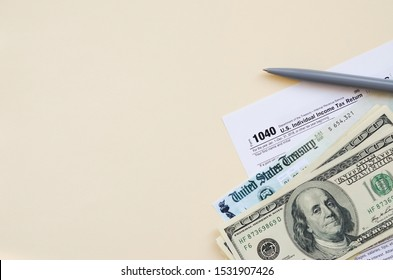 1040 Individual Income tax return form with Refund Check and hundred dollar bills on beige background