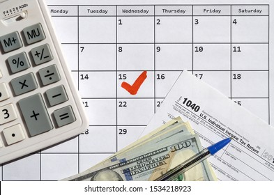 1040 Individual Income Tax Return blank with dollar bills, calculator and pen on calendar page with marked 15th April
