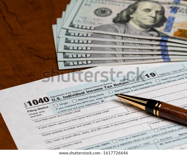 1040 individual income tax return form 2019 with ballpoint pen and 100 dollar bills. Concept of filing taxes, payment, refund, and April 15, 2020 deadline date