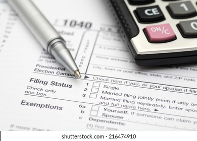 1040 Tax Form with calculator and ball point pen.