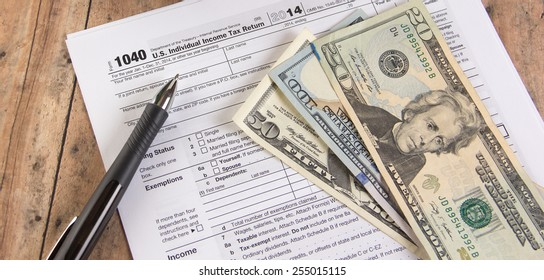 1040 tax form with calculator and dollar bills