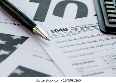 1040 tax form, calculator and pen on the table