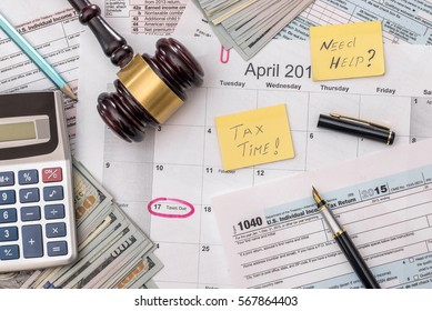 1040 tax form with gavel and dollars and pen.