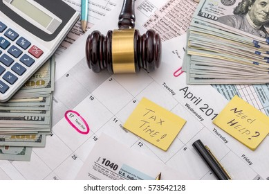 1040 tax form with hammer, money, pen and calculator