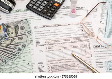 1040 tax form  with pen, dollar and calculator