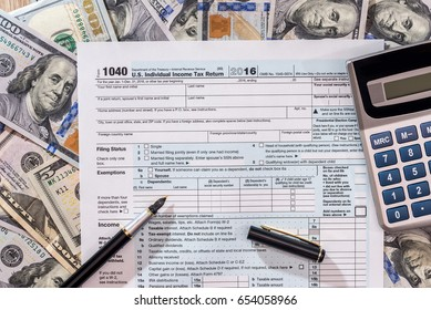 1040 tax from with us dollar banknote, pen and calculator.