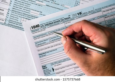1040 us individual income tax return form with hand holding pen over. Filling out form and deadline concept.