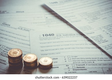 1040 US tax form with coins. Taxation concept